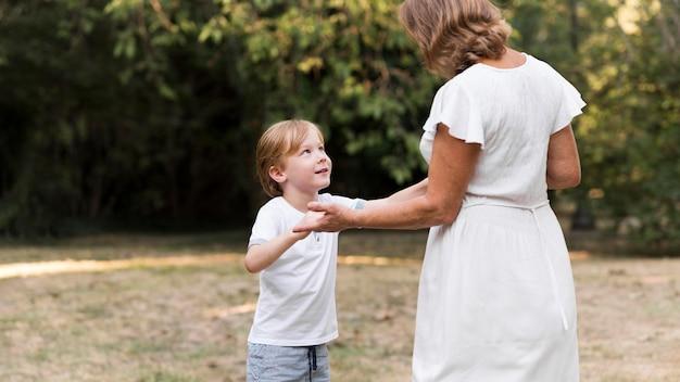 Średnio ujęcie babci i dziecka trzymających się za ręce