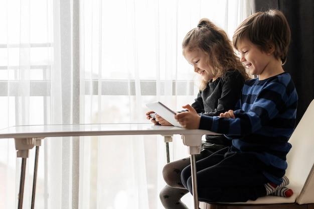 Średnio ujęcie dzieci siedzących na krzesłach