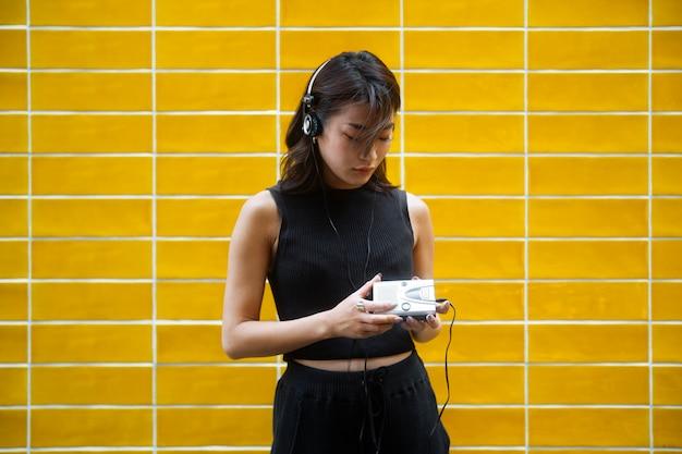 Średnio ujęcie japońskiej kobiety słuchającej muzyki