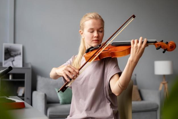 Średnio ujęcie kobiety grającej na skrzypcach