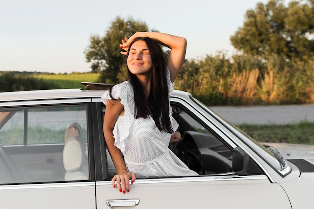 Średnio ujęcie kobiety pozującej przez okno