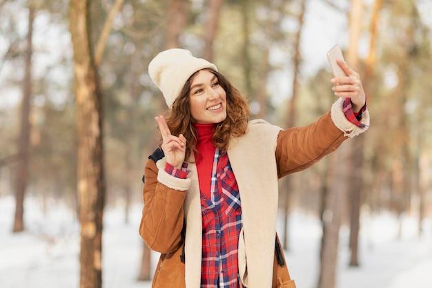 Średnio ujęcie kobiety robiące selfie
