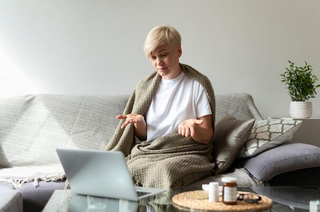 Średnio ujęcie kobiety siedzącej na kanapie