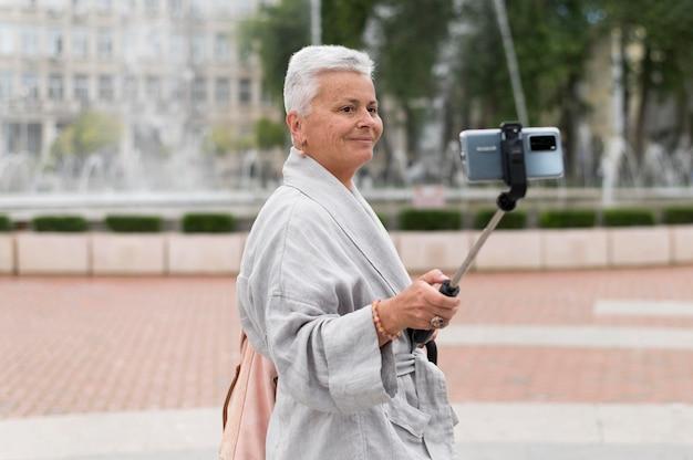 Średnio ujęcie kobiety trzymającej kij do selfie