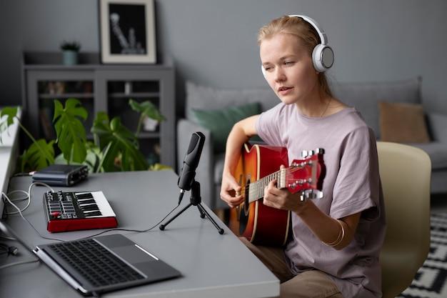Średnio ujęcie kobiety tworzącej muzykę w domu