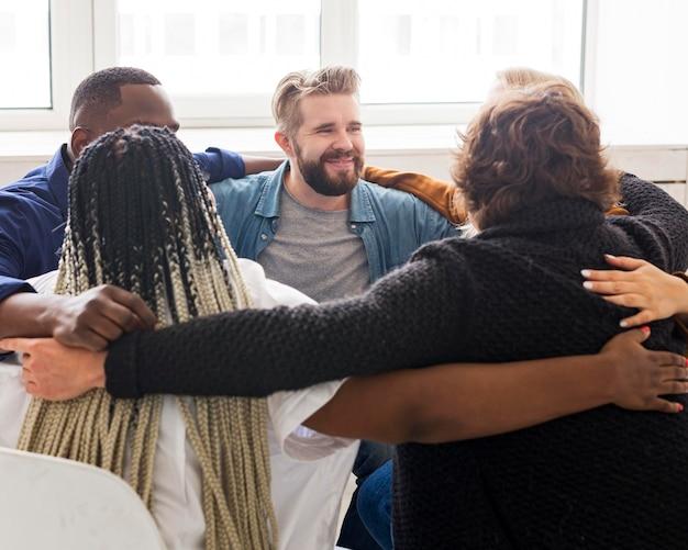 Średnio ujęcie osób przytulających się na spotkaniu