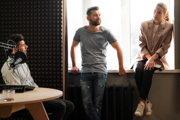 Średnio ujęcie osób rozmawiających w stacji radiowej