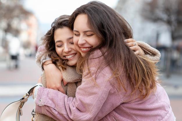 Średnio ujęcie przytulających się uśmiechniętych przyjaciół