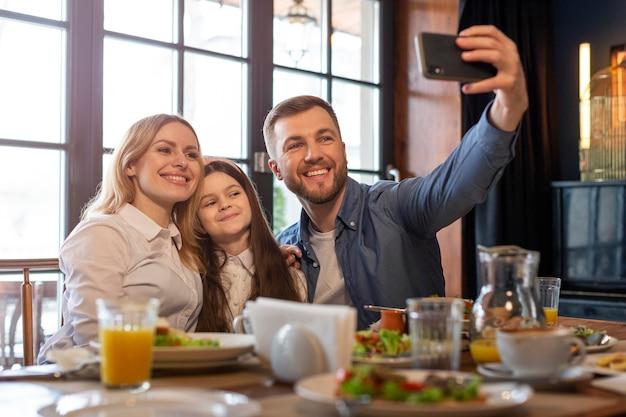 Średnio ujęcie rodziny robiącej selfie
