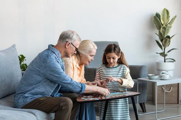 Średnio ujęcie rodziny układającej puzzle