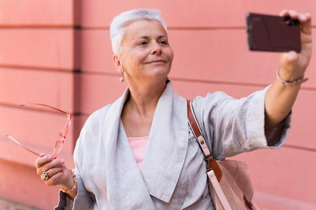 Średnio ujęcie stara kobieta robi selfie