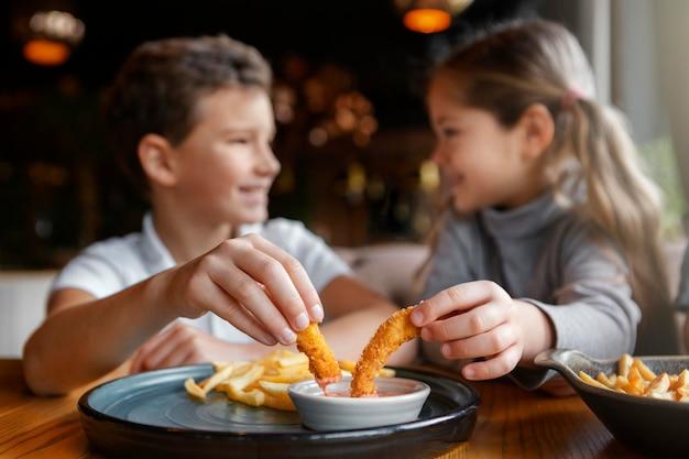 Średnio ujęcie uśmiechniętych dzieci jedzących razem