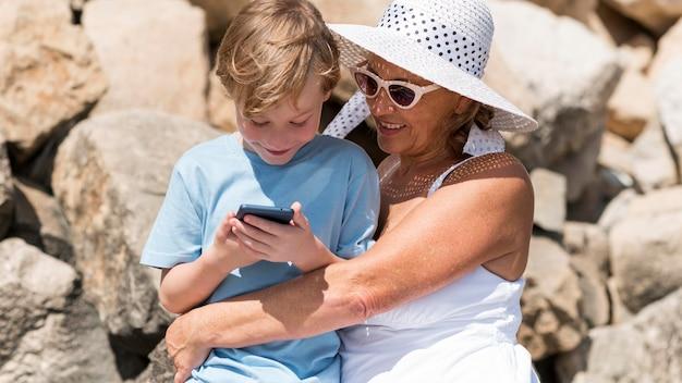 Średnio ujęta babcia i dziecko z telefonem