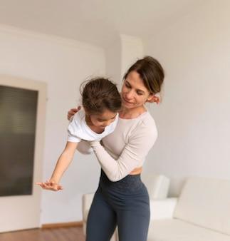 Średnio ujęta kobieta i dziecko ćwiczą