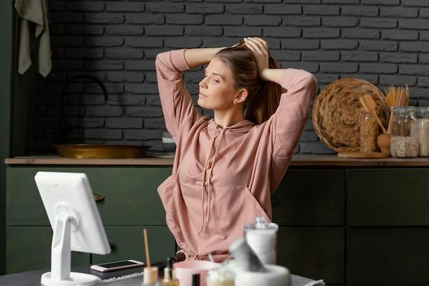 Średnio ujęta kobieta wiążąca włosy w pomieszczeniu