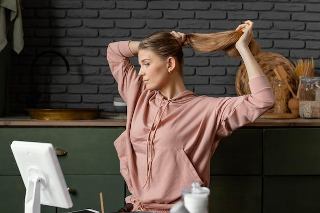 Średnio ujęta kobieta wiążąca włosy