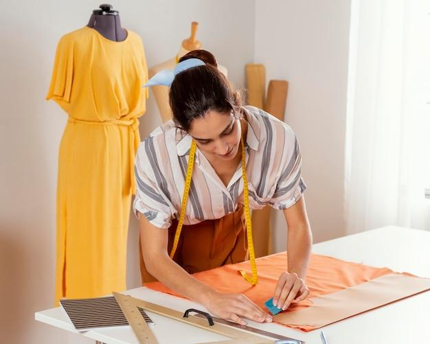Średnio ujęta kobieta znakująca tkaninę