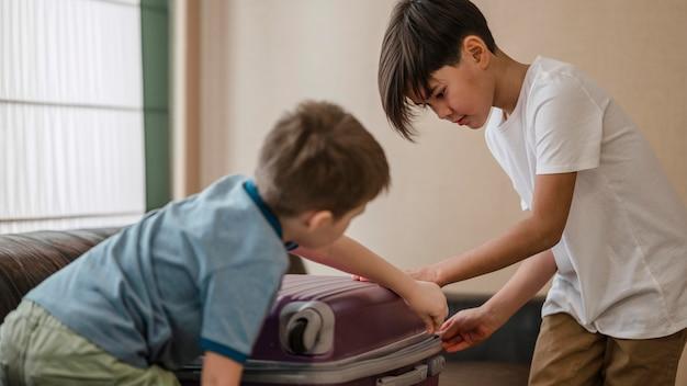 Średnio ujęte dzieci pakujące się razem