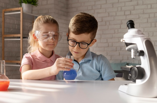 Średnio ujęte dzieci przeprowadzające eksperymenty