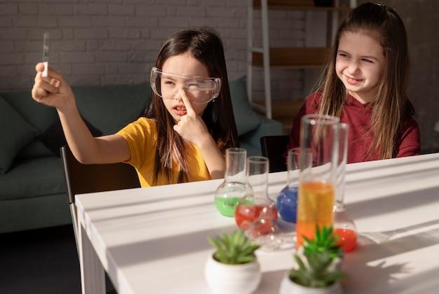 Średnio ujęte dziewczyny naukowe ze szklanym szkiełkiem