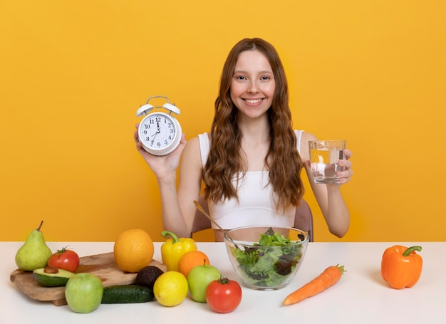 Średnio ustrzelona kobieta z jedzeniem i zegarem