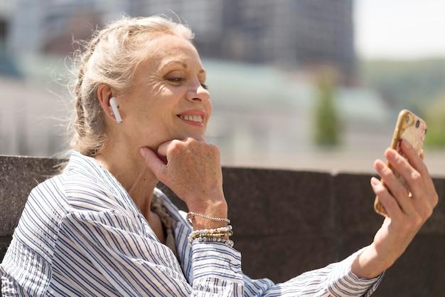 Średnio ustrzelona starsza kobieta ze smartfonem