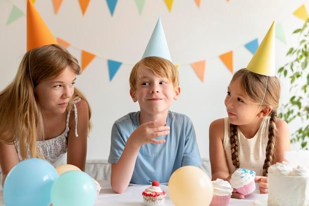 Średnio ustrzelone dzieci w czapkach imprezowych