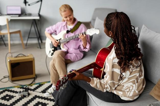 Średnio ustrzelone kobiety grające na gitarze