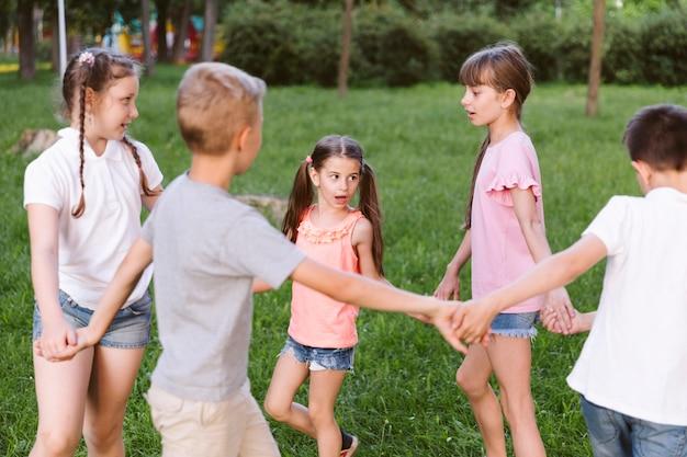 Średnio wystrzelone dzieciaki trzymające ręce