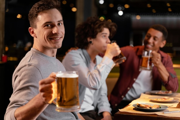 Średnio zastrzeleni mężczyźni pijący piwo