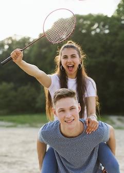 Średnio zastrzeleni przyjaciele bawią się z rakietką do badmintona