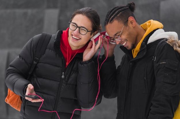 Średnio zastrzeleni przyjaciele słuchający muzyki razem