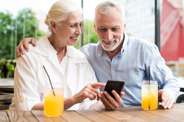 Średnio zastrzeleni starzy ludzie patrząc na telefon