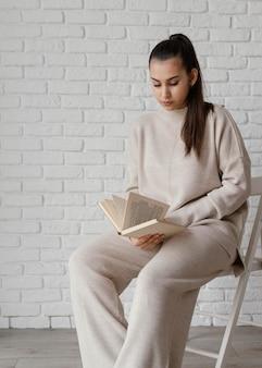 Średnio zastrzelona kobieta na krześle do czytania