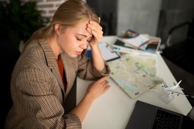 Średnio zastrzelona zmęczona kobieta w biurze podróży