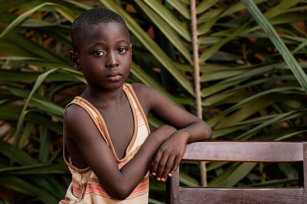 Średnio zastrzelone dziecko pozujące z krzesłem