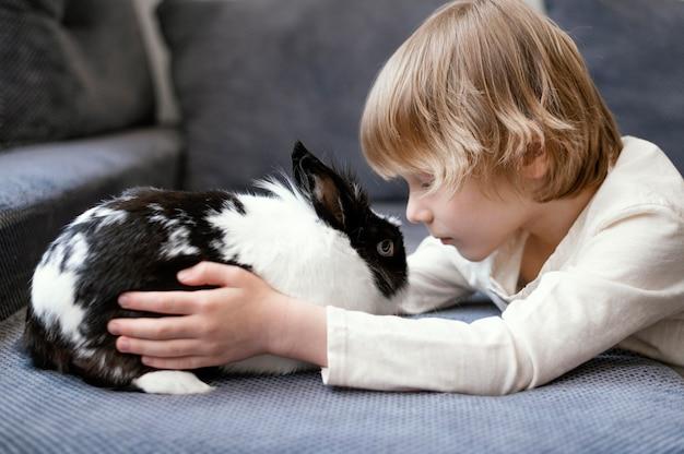 Średnio zastrzelony chłopiec z uroczym króliczkiem