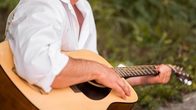 Średnio zastrzelony mężczyzna gra na gitarze w naturze