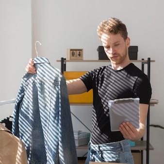 Średnio zastrzelony mężczyzna inwentaryzujący ubrania