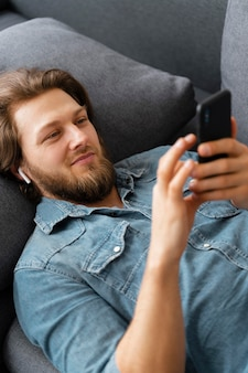 Średnio zastrzelony mężczyzna na kanapie ze smartfonem