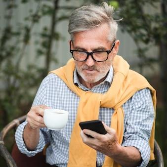 Średnio zastrzelony mężczyzna patrząc na smartfona