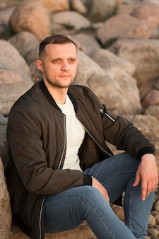 Średnio zastrzelony mężczyzna siedzący na skałach