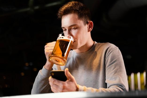 Średnio zastrzelony mężczyzna z telefonem i kuflem piwa