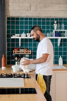 Średnio zastrzelony mężczyzna zmywa naczynia
