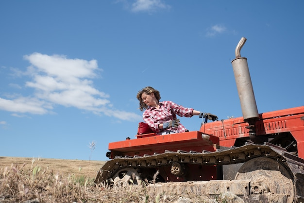 Średniorolna kobieta jedzie ciągnika w polu