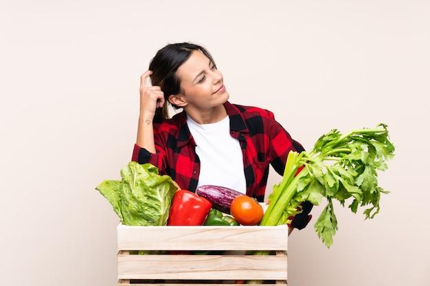 Średniorolna kobieta trzyma świeżych warzywa w drewnianym koszu ma wątpliwości i wprawiać w zakłopotanie twarz wyrażenie