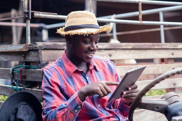 Średniorolny mężczyzna używa pastylkę z szczęśliwym i uśmiechniętym na starym ciągniku