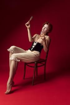 Średniowieczna ruda młoda kobieta jako księżna w czarnym gorsecie i nocnych ubraniach siedzi na czerwono