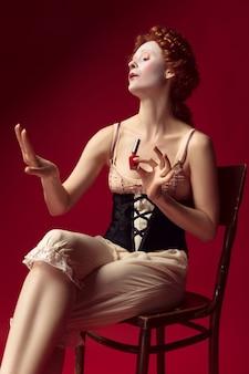 Średniowieczna ruda młoda kobieta jako księżna w czarnym gorsecie i nocnym stroju siedzi na krześle na czerwonej ścianie. używanie lakieru do paznokci. pojęcie porównania epok, nowoczesności i renesansu.