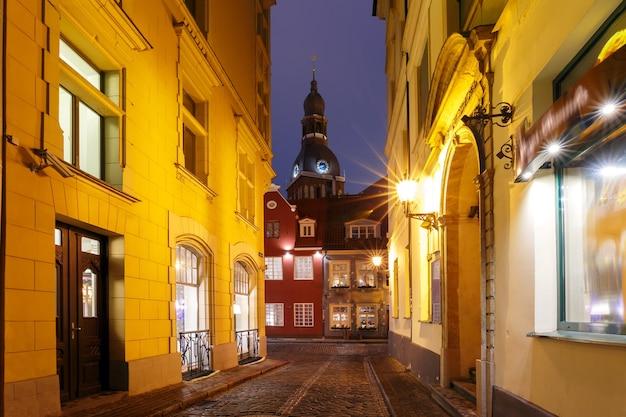 Średniowieczna ulica i katedra najświętszej marii panny w nocy, ryga, łotwa